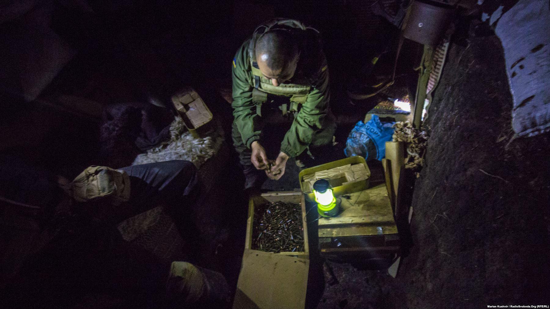 Солдат споряджає набоями ріжки автоматів у бліндажі на передовій біля Попасної