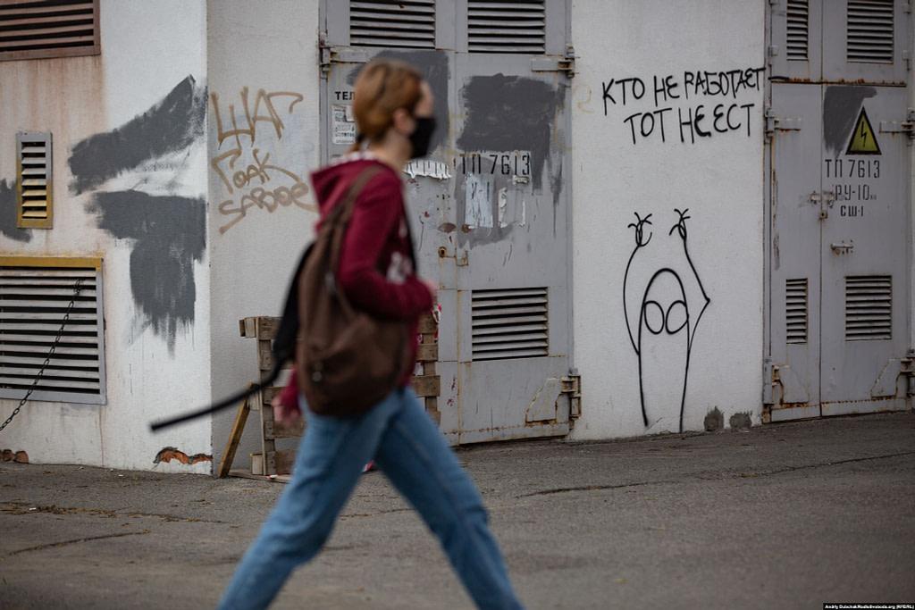 Дівчина проходить повз трансформаторну будку з графіті «Хто не працює, той не їсть». Фото - Андрій Дубчак