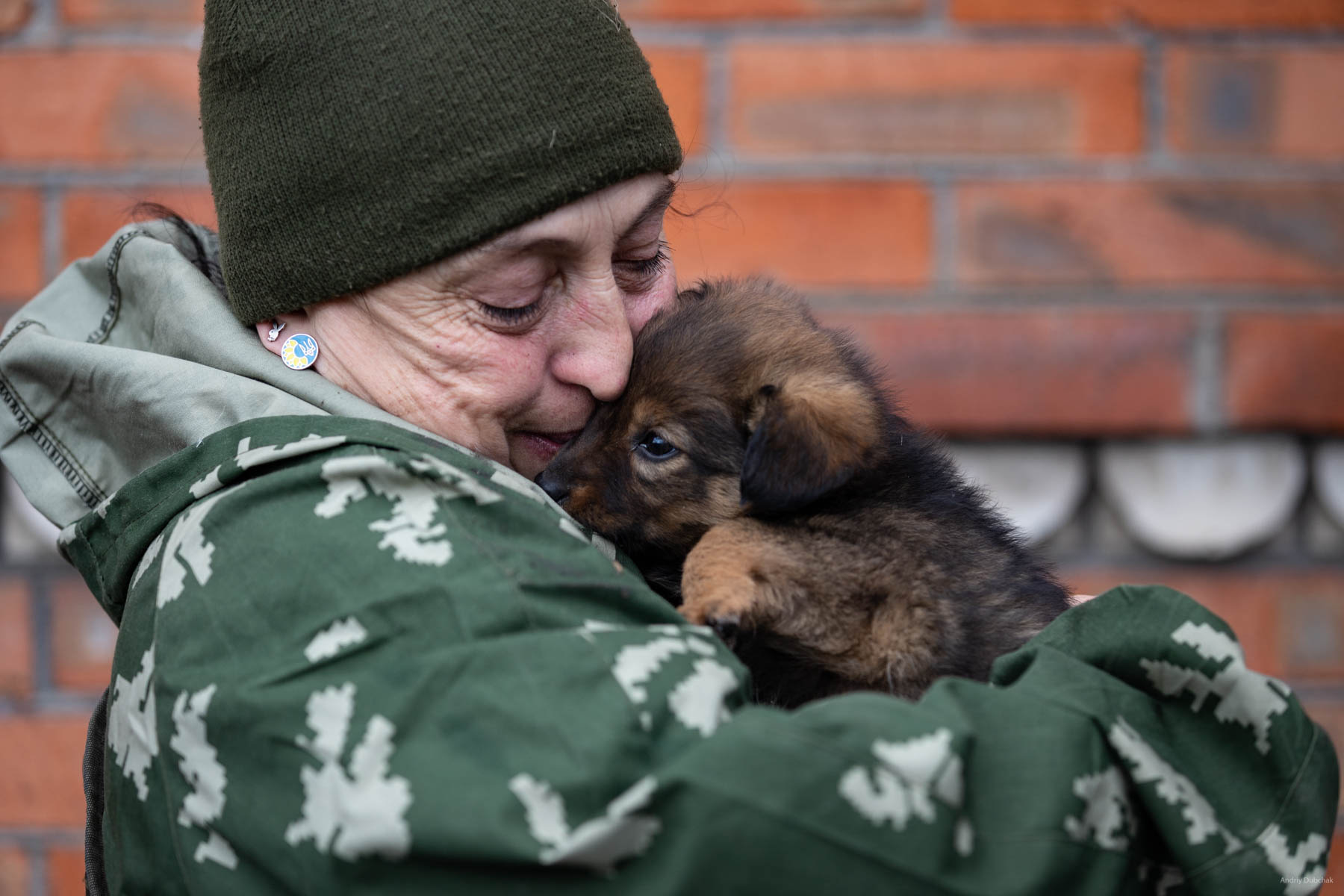 "A combat medic, ""Viktorovna,"" is playing with Fly the puppy, before traveling to a concert in Mariupol. Soldiers prepare food themselves. Since the boys are mostly young, they often eat ""what is available"", ""not bothering"" themselves with cooking. Probably, that is why a single woman here, the combat medic of the company, ""Victorovna"", who always cooks a lot of very tasty foodstuff, has guests in the house all the time, especially in the kitchen ... :) In all the shelters and basements, many animals (cats, dogs) live with fighters. As a rule, if there are dogs - there are no cats. And vice versa. Shirokine, March 2018."