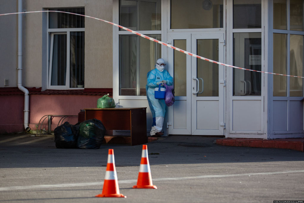 A medical worker collects supplies dropped off at Kalynivka's hospital. The facility is now effectively sealed off from the outside world. Waste is picked up and supplies are dropped off by people who avoid direct contact with the staff inside. Photographer Andriy Dubchak / Ukraine