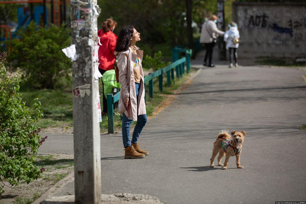 Дівчина, яка вигулює песика, підставляє обличчя весняному сонцю. Фото - Андрій Дубчак