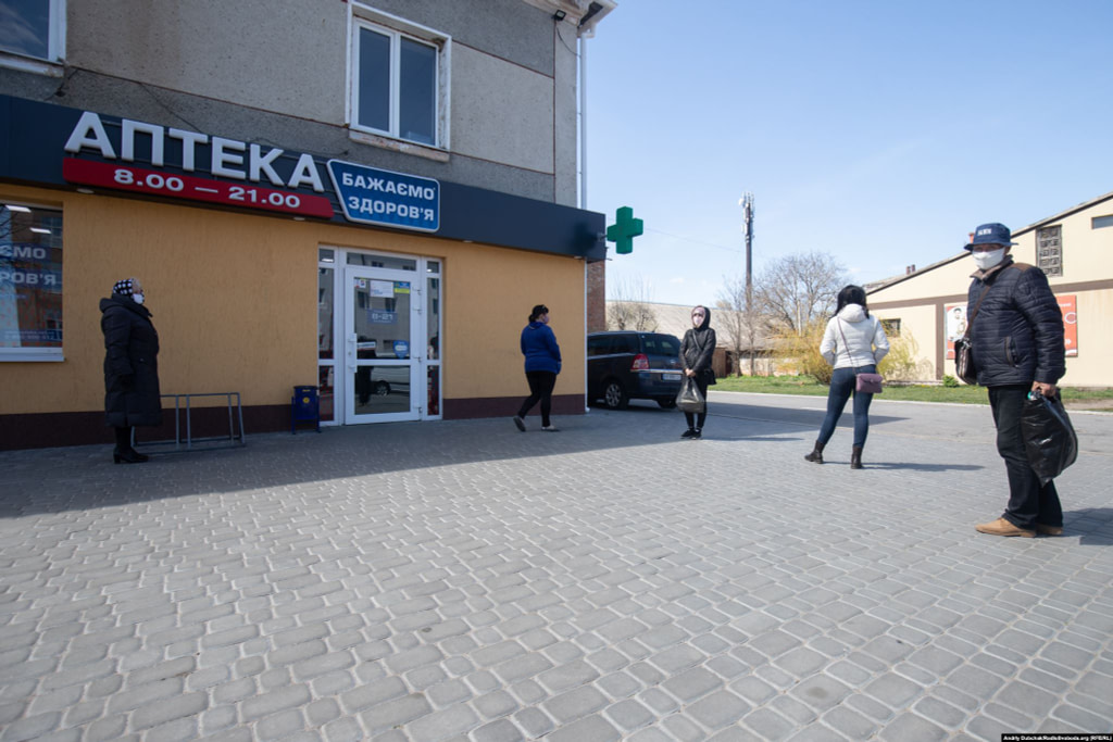 "Locals keep their distance as they wait in line outside a pharmacy. One resident of Kalynivka said the town's elderly residents initially poked fun at people wearing face masks ""then, as the situation developed, everyone quickly adopted [the masks]."" Photographer Andriy Dubchak / Ukraine"