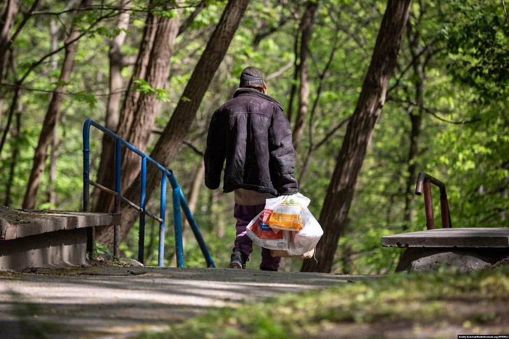 Безхатченко з пакетами прямує з території «Павлівської» лікарні у Кирилівській гай / Фото - Андрій Дубчак