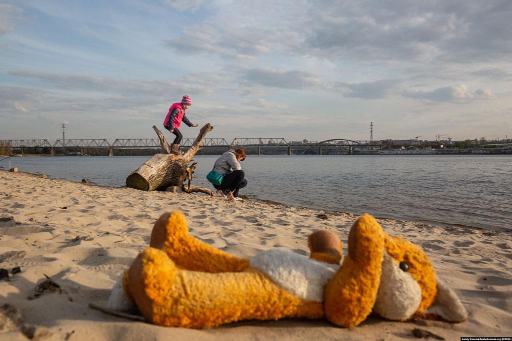 Мати з донькою гуляють на майже безлюдному березі Дніпра. Фото - Андрій Дубчак