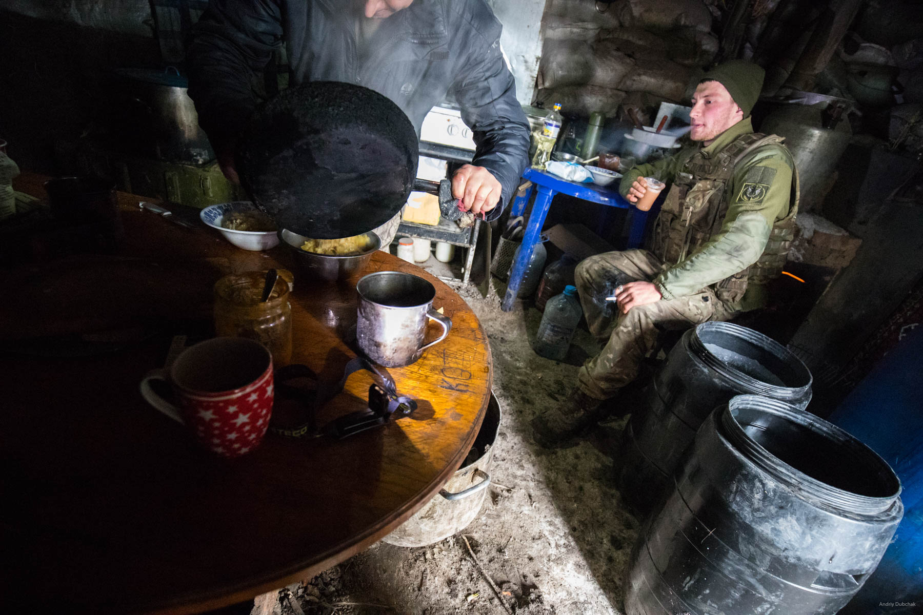 "A marine drinks coffee and smokes in a kitchen-dugout, near Shirokine. Local ""club"" - a kitchen, some people are always there, the place you can eat at(they cook all the time), drink coffee with a cigar (almost everyone smokes), talk. Usually there is good Wi-Fi. Shirokine, March 2018."