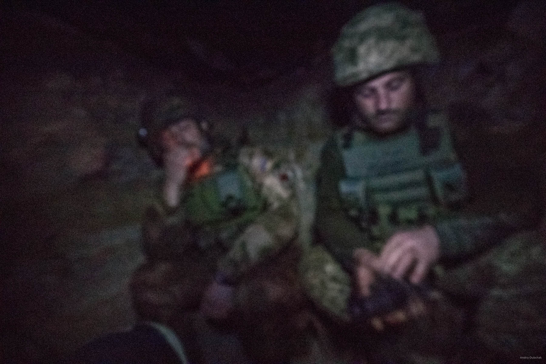 "Night at ""observer.""   In total darkness of a dugout, Mykhajlo smokes, while on watch on his frontline position. Experienced ""Didick"" is to the right of him.  Night turns out to be quiet. We are having a conversation. Repeatedly, in total darkness, either Mykhajlo or ""Didick"" stands up and look out through a gun-slot. A night vision scope helps to monitor the situation. ""We regularly experience ""nightmares"": 12,7 millimeters, sometimes 14,5 and 7,62 all the time. There were cases, when 5,45 mm bullets flayed in through the gun-slot,"" says Didick, fidgeting with a night vision scope. 'When I come home, the question that strikes me most - ""When will the war end?"" How do I know? We do everything what depends from us. However, there is one thing that I will never get used to – when you have to inform relatives that their son, or husband, or other family member is no more. When that mobile rings and you have to answer, and you can hear a female voice saying, ""Hello! Hello! Sashku, Sashku, how you? Hello! Why are you silent?"" Moreover, you stand there, not knowing with what to begin. You talk some nonsense, trying to express your apologies and sympathies. In such moments, my voice trembled, with hands and feet wobbly. There would be silence on the other end. Then you would hear weeping and hysterics. That was the hardest thing,"" recalls Mykhajlo. Sometime later, there is a flare in total darkness. Sound follows in a few seconds. It is an ""exit."" Guys monitor the situation. Enemy fired AT mounted grenade launcher at positions of an adjacent friendly brigade.  District of Popasnoy, December 2017"