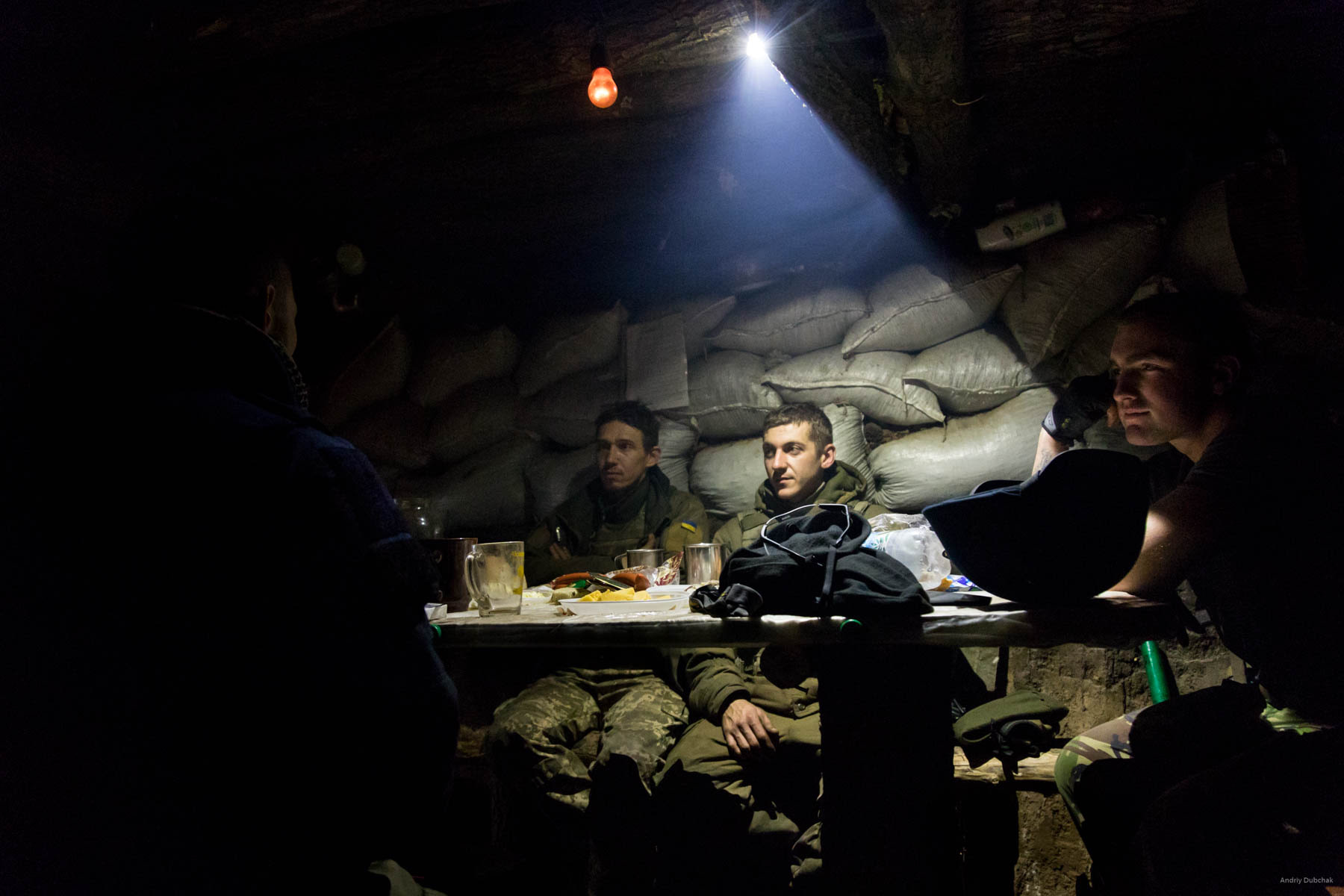 Supper during a fight. Ukrainian soldiers dine in a dugout on the front, near Popanskaya, while other fighters suppress the enemy's fire. The enemy, in some way, learned about our arrival to the position (it was found out from the radio interception). That night, we were shot at three times from small arms. District of Popasnoy, December 2017 Read and watch: https://goo.gl/SeMPXb