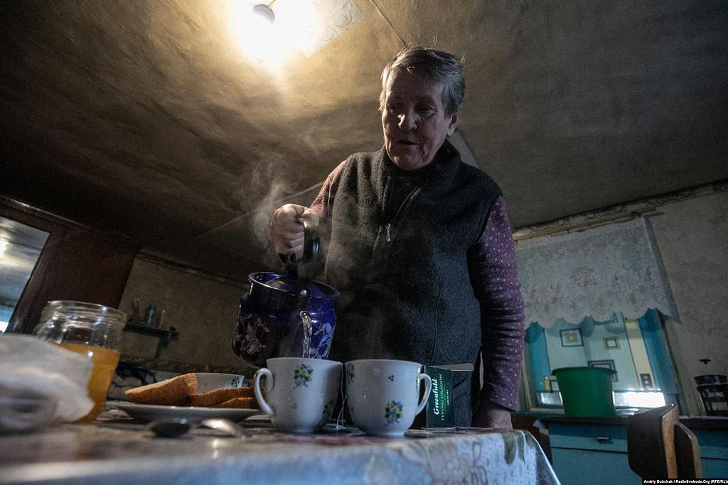 Жителька Катеринівки баба Люба розповідає про ситуацію в селі. Вже пару днів, каже вона, зовсім тихо і не стріляють. Вона «за розведення», і «аби ж не стріляли». Але й у «сірій зоні» вона жити не хоче і каже, що якби їй держава запропонувала виїхати звідси, вона б погодилася.  Золоте (фотограф Андрій Дубчак)