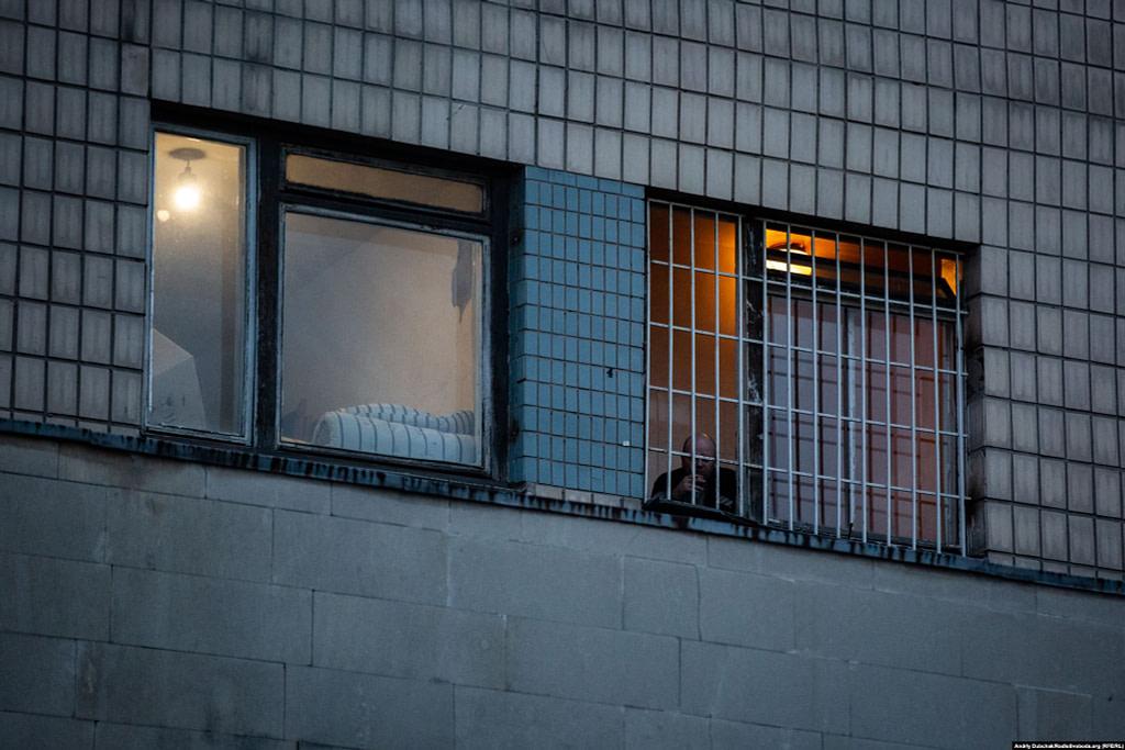 Чоловік курить за гратами вікна одного з корпусів лікарні / Фото - Андрій Дубчак