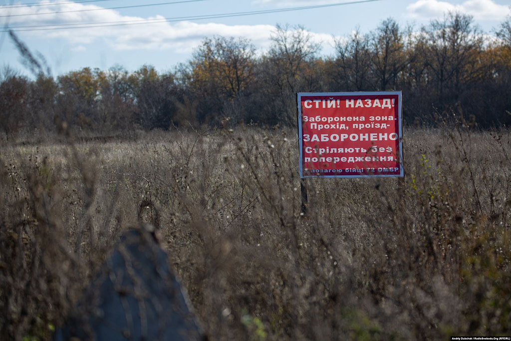 """We walk from Zolote-4 to Katerynivka; part of the road is in the """"grey zone"""". To the left of the road are signs, politely warning passers-by that they might be shot at without warning (Ukraine reporter Andriy Dubchak)"""