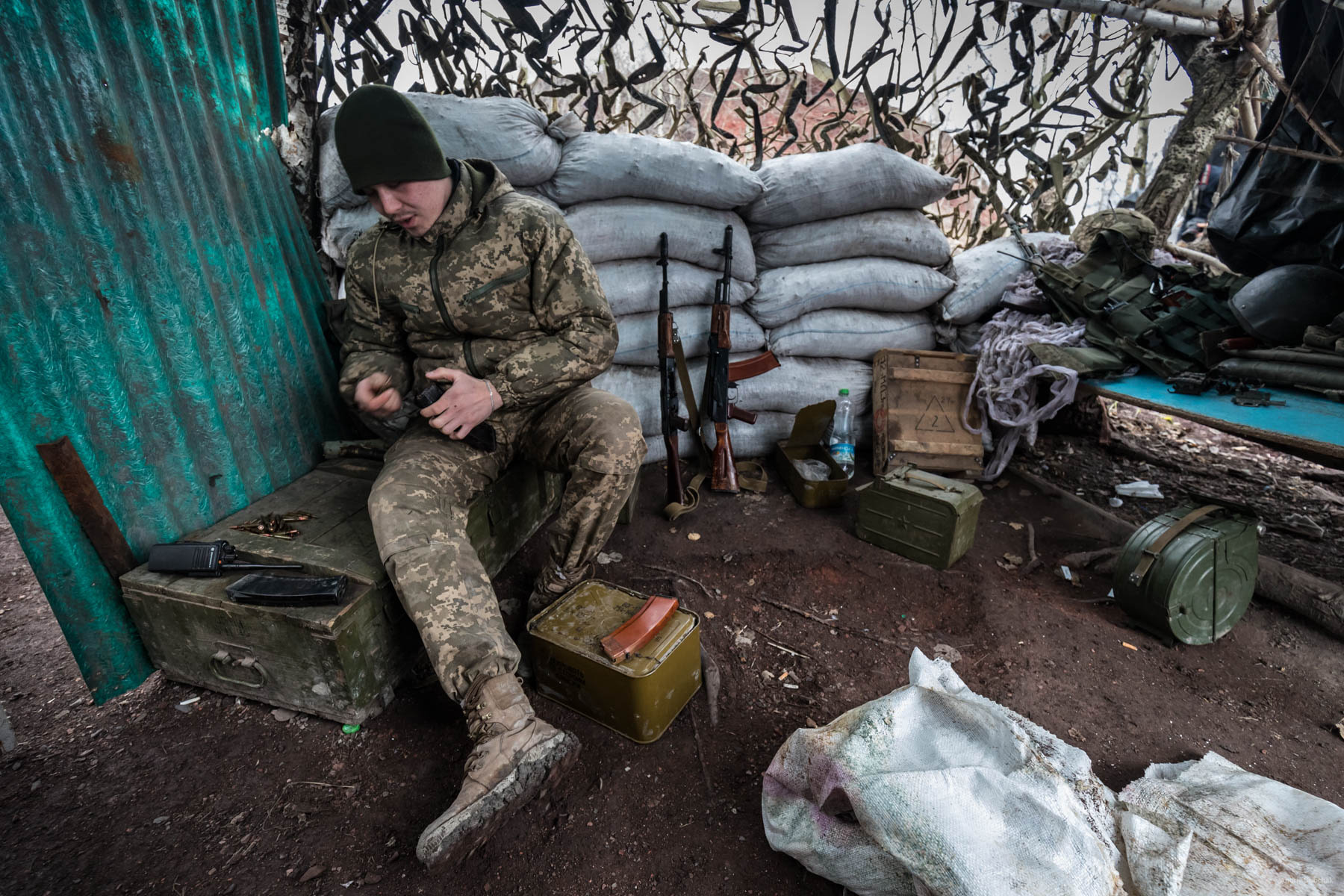 "Alexander, a fighter from Kherson, reloads his assault rifle dispenser magazine on a position reinforced with refuse stone bags, on the gob pile near a town Zolote. - Do you want to go home? Sasha smiles: - I feel sad at home. In addition, here are our boys. It's OK.  The guy is 20 years old. In a conversation, he often uses the phrase ""It's OK.""    District of Popasnoy, December 2017"