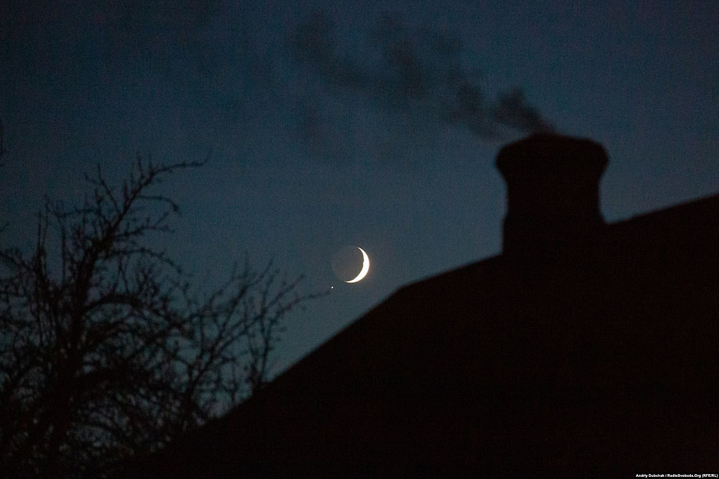 """We completed our visit and photo report. Leaving the area, we saw the crescent moon starkly outlined in the dark sky over """"grey"""" Katerynivka. It was quiet… (photographer Andriy Dubchak)"""