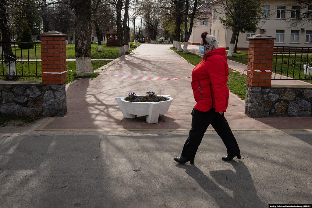 Жінка у медичній масці проходить повз закритого обмежувальною стрічкою входу до Калинівської лікарні. Фото - Андрій Дубчак
